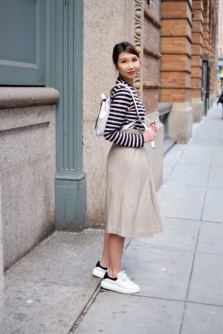 Look de moda: Camiseta de manga larga de lentejuelas de rayas horizontales en blanco y negro, Falda midi plisada en beige, Tenis de cuero en blanco y negro, Mochila de cuero blanca