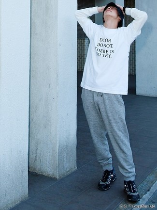 Cómo combinar: camiseta de manga larga estampada en blanco y negro, pantalón de chándal gris, deportivas negras, gorro de pescador negro