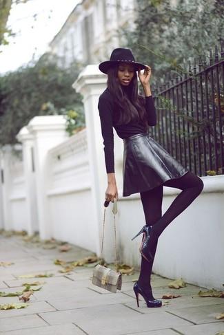 Cómo combinar: camiseta de manga larga negra, falda skater de cuero negra, zapatos de tacón de cuero negros, bolso bandolera de cuero con print de serpiente gris