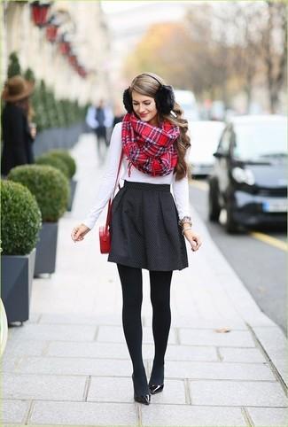 Elige una camiseta de manga larga blanca y una falda skater a lunares negra para una apariencia fácil de vestir para todos los días. Zapatos de tacón de cuero negros levantan al instante cualquier look simple.