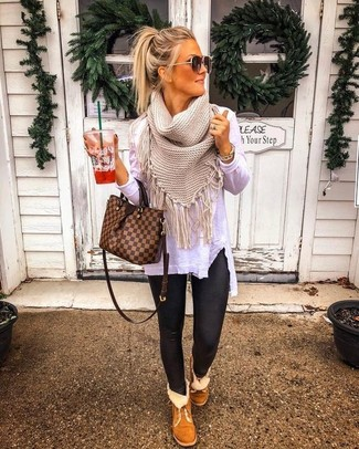Este combinación de una camiseta de manga larga blanca y unos leggings de cuero negros te da una onda muy informal y accesible. Botas ugg marrónes añadirán un nuevo toque a un estilo que de lo contrario es clásico.