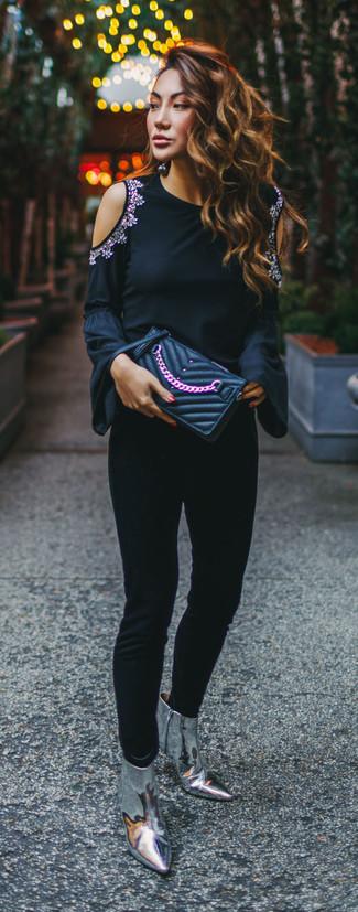 Cómo combinar: camiseta de manga larga con adornos negra, pantalones pitillo negros, botines de cuero plateados, cartera sobre de cuero acolchada negra