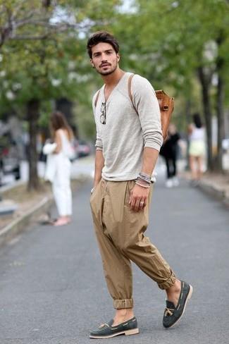 Cómo combinar: camiseta de manga larga gris, pantalón chino marrón claro, mocasín con borlas de ante azul marino, mochila de cuero en tabaco