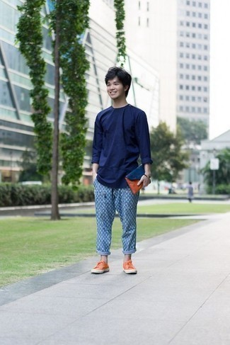 Moda para hombres adolescentes: Emparejar una camiseta de manga larga azul marino y un pantalón chino estampado azul es una opción cómoda para hacer diligencias en la ciudad. Tenis de lona naranjas son una opción atractiva para complementar tu atuendo.