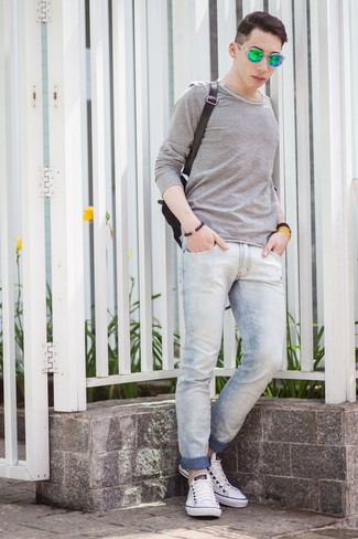 Cómo combinar: camiseta de manga larga gris, vaqueros pitillo celestes, tenis blancos, mochila de lona negra