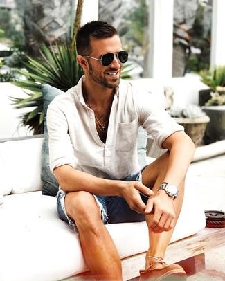 Cómo combinar: camiseta henley de manga larga en beige, pantalones cortos vaqueros desgastados azules, náuticos de cuero marrónes, gafas de sol negras