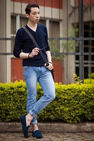 Cómo combinar: camiseta henley de manga larga azul marino, vaqueros pitillo celestes, mocasín de ante azul marino, bolso mensajero de cuero negro