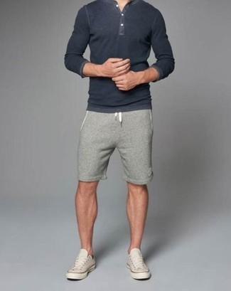 Cómo combinar: camiseta henley en gris oscuro, pantalones cortos grises, tenis en beige