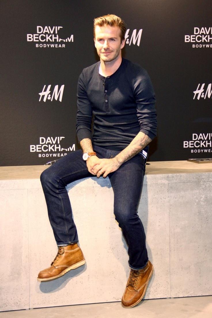 Look de David Beckham Camiseta Henley Negra, Vaqueros Azul Marino, Botas de Cuero