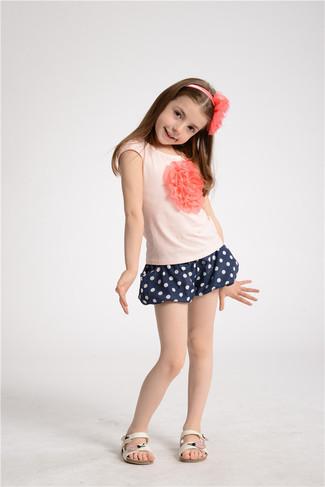 Cómo combinar: camiseta rosada, pantalones cortos a lunares azul marino, sandalias blancas, cinta para la cabeza rosada