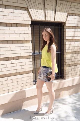Cómo combinar: camiseta sin manga amarilla, minifalda estampada azul, zapatos de tacón de cuero con print de serpiente grises, cartera sobre de cuero con tachuelas negra