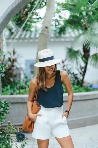 Cómo combinar: camiseta sin manga azul marino, pantalones cortos blancos, bolsa tote de cuero marrón claro, sombrero de paja blanco
