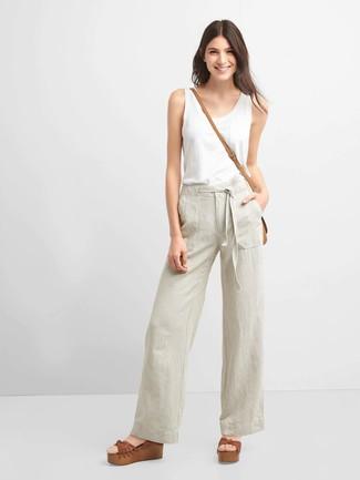 Una camiseta y unos pantalones anchos en beige son prendas que debes tener en tu armario. Sandalias con cuña de cuero marrónes son una opción grandiosa para complementar tu atuendo.