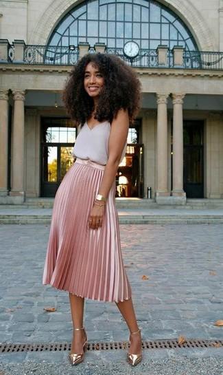 Cómo combinar: camiseta sin manga de gasa gris, falda midi plisada rosada, zapatos de tacón de cuero dorados, reloj dorado