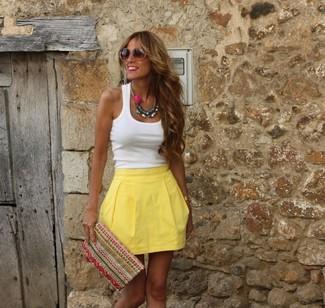 Cómo combinar: camiseta sin manga blanca, falda skater amarilla, cartera sobre bordada en multicolor, gafas de sol marrónes