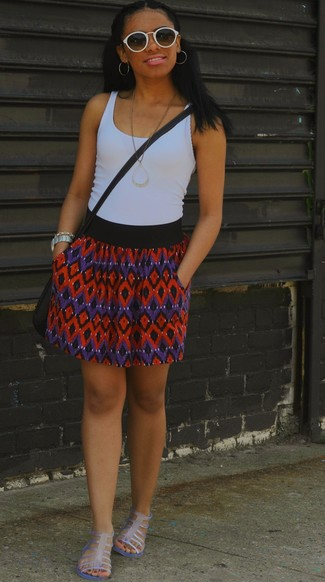 Cómo combinar: camiseta sin manga blanca, falda skater en zig zag en rojo y azul marino, sandalias romanas de goma transparentes, bolso bandolera de cuero negro