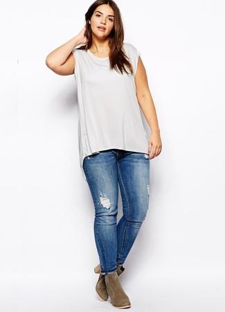 Cómo combinar: camiseta sin manga gris, vaqueros pitillo desgastados azules, botines de ante verde oliva
