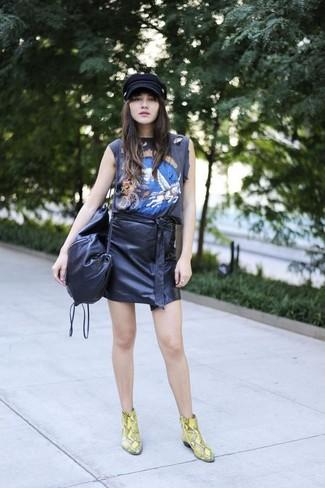 Una camiseta sin manga estampada negra y una minifalda de cuero negra son una opción incomparable para el fin de semana. ¿Te sientes valiente? Elige un par de botines de cuero de serpiente amarillos.