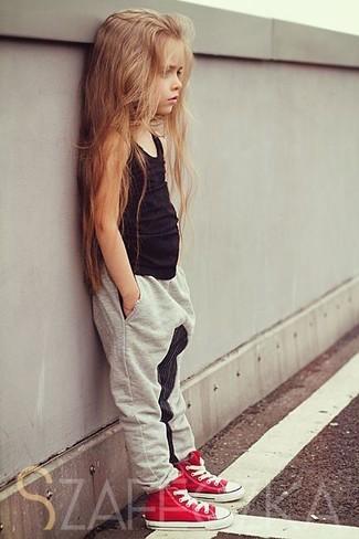 Cómo combinar: camiseta sin manga negra, pantalones grises, zapatillas rojas