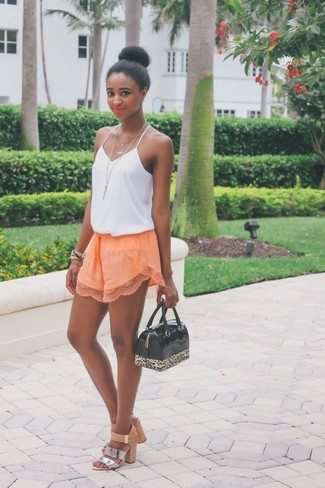 Elige por la comodidad con una camiseta sin manga de seda blanca y unos pantalones cortos naranjas. ¿Por qué no ponerse sandalias de tacón de cuero plateadas a la combinación para dar una sensación más clásica?