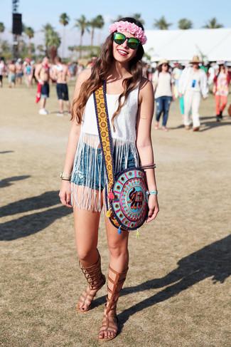 Cómo combinar: camiseta sin manga сon flecos blanca, pantalones cortos vaqueros azules, sandalias romanas altas de cuero marrónes, bolso bandolera bordado en multicolor