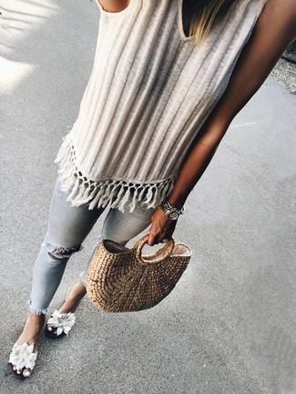 Cómo combinar: camiseta sin manga de punto blanca, vaqueros pitillo desgastados celestes, sandalias planas de lona con print de flores blancas, bolsa tote de paja marrón claro