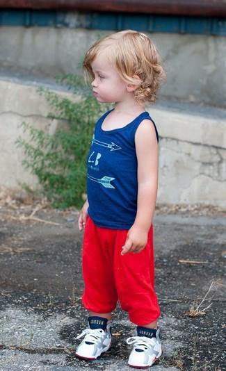 Cómo combinar: camiseta sin mangas azul, pantalón de chándal rojo, zapatillas blancas