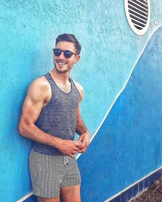 Look de moda: Camiseta sin mangas en gris oscuro, Shorts de baño estampados en blanco y negro, Gafas de sol negras