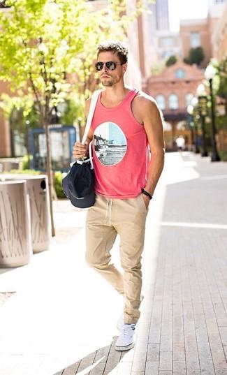 Cómo combinar: camiseta sin mangas estampada rosada, pantalón de chándal en beige, zapatillas plimsoll blancas, bolso baúl de lona en negro y blanco