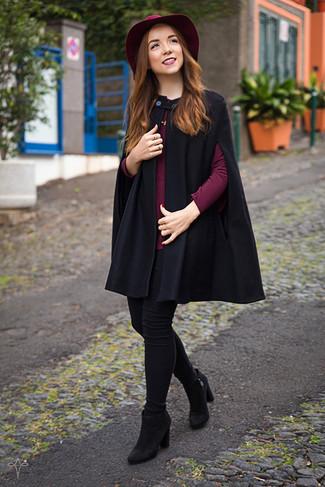Cómo combinar: capa negra, blusa de manga larga burdeos, vaqueros pitillo negros, botines de ante negros