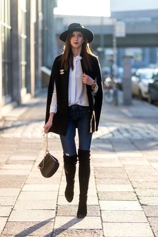 Cómo combinar: capa negra, camisa de vestir de seda blanca, vaqueros pitillo azul marino, botas sobre la rodilla de ante negras