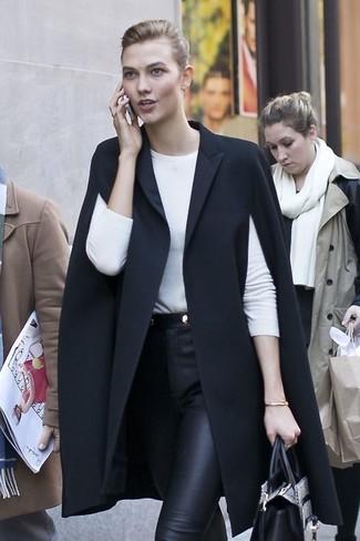 Cómo combinar: capa negra, camiseta de manga larga blanca, pantalones pitillo de cuero negros, bolsa tote de cuero con print de serpiente gris