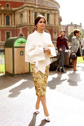 Intenta ponerse una capa en beige y una falda lápiz de lentejuelas dorada para lograr un look de vestir pero no muy formal. Zapatos de tacón de cuero con recorte blancos son una opción práctica para completar este atuendo.