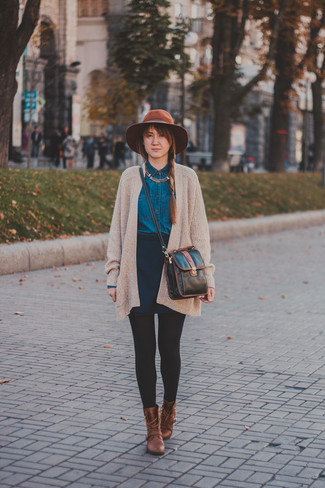 Cómo combinar: cárdigan abierto de punto en beige, camisa vaquera azul marino, falda skater azul marino, botas planas con cordones de cuero marrónes
