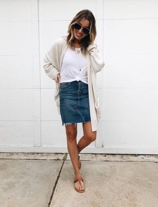 Cómo combinar: cárdigan abierto en beige, camiseta con cuello circular blanca, minifalda vaquera azul marino, sandalias de dedo de cuero marrónes