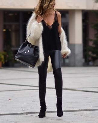 Cómo combinar: cárdigan abierto de angora blanco, camiseta sin manga de seda negra, leggings de cuero negros, botines de ante negros
