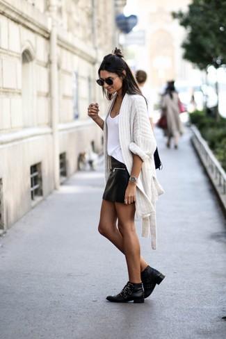 Cómo combinar: cárdigan abierto de punto blanco, camiseta sin manga blanca, minifalda de cuero negra, botines de cuero con tachuelas negros