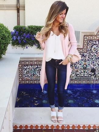 Cómo combinar: cárdigan abierto rosado, camiseta sin manga de seda blanca, vaqueros pitillo azul marino, sandalias de tacón de cuero blancas