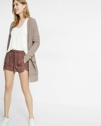 Cómo combinar: cárdigan abierto de punto en beige, camiseta sin manga blanca, pantalones cortos marrónes, tenis blancos