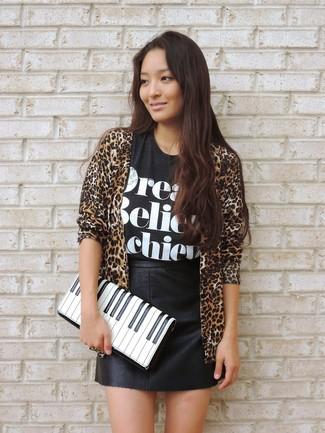 Cómo combinar: cárdigan abierto de leopardo marrón claro, camiseta con cuello circular estampada en negro y blanco, minifalda de cuero negra, cartera sobre de cuero estampada en blanco y negro
