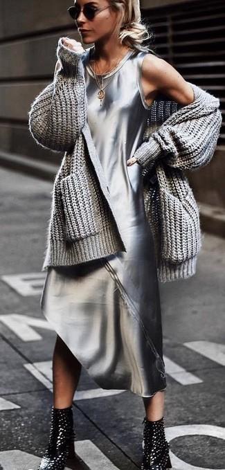 Cómo combinar: cárdigan abierto de punto gris, vestido de tirantes plateado, botines de cuero con tachuelas negros, gafas de sol negras