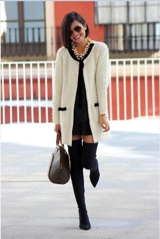 Cómo combinar: cárdigan abierto de punto en blanco y negro, vestido recto negro, botas sobre la rodilla de ante negras, bolsa tote de cuero estampada en marrón oscuro