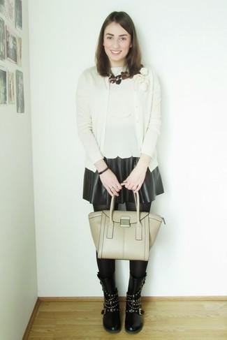 Cómo combinar: cárdigan en beige, blusa sin mangas en beige, falda skater de cuero negra, botas a media pierna de cuero con tachuelas negras