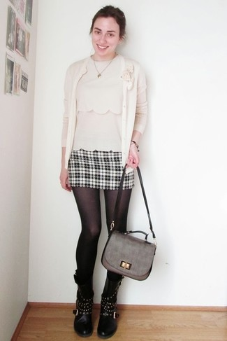 Cómo combinar: cárdigan en beige, blusa sin mangas en beige, minifalda de tartán en negro y blanco, botas a media pierna de cuero con tachuelas negras