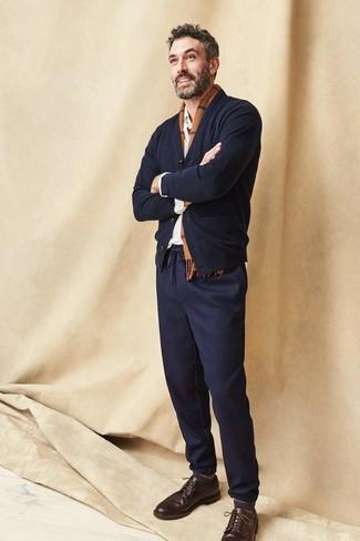 Cómo combinar: cárdigan negro, camisa de manga larga blanca, pantalón chino azul marino, zapatos brogue de cuero en marrón oscuro