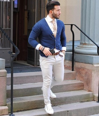 Cómo combinar: cárdigan azul marino, camisa de vestir blanca, pantalón chino blanco, tenis de cuero blancos