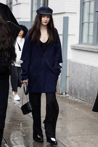 Cómo combinar: cárdigan grueso azul marino, camiseta con cuello circular negra, pantalón de campana negro, botines de cuero en negro y blanco