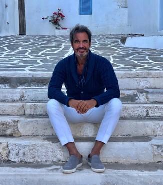 Cómo combinar: cárdigan con cuello chal azul marino, camisa de manga larga de rayas verticales azul marino, pantalón chino blanco, zapatillas slip-on de ante grises
