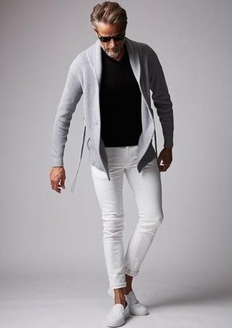 Cómo combinar una camiseta con cuello en v negra: Para crear una apariencia para un almuerzo con amigos en el fin de semana ponte una camiseta con cuello en v negra y unos vaqueros blancos. Con el calzado, sé más clásico y opta por un par de zapatillas slip-on de lona blancas.