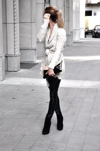 Cómo combinar: cárdigan con cuello chal en beige, leggings de cuero negros, botines con cuña de ante negros, cartera sobre de cuero en negro y blanco